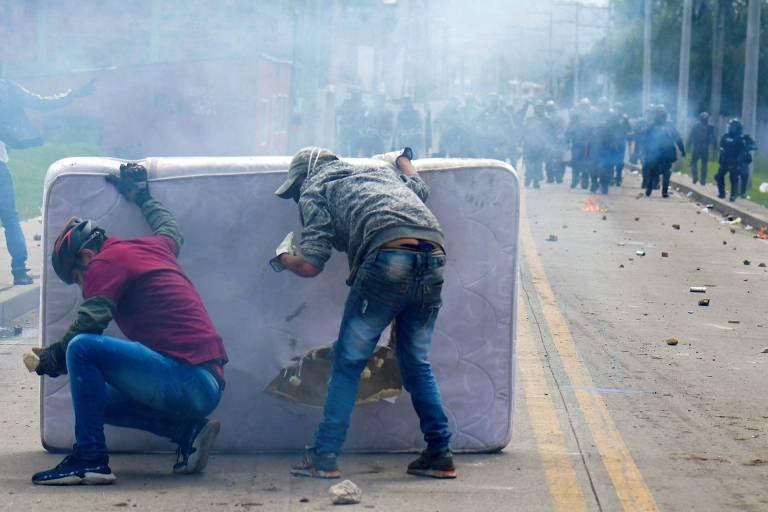 Manifestantes se protegem atrás de colchão durante conflito com policiais em protesto em Facatativa, na Colômbia