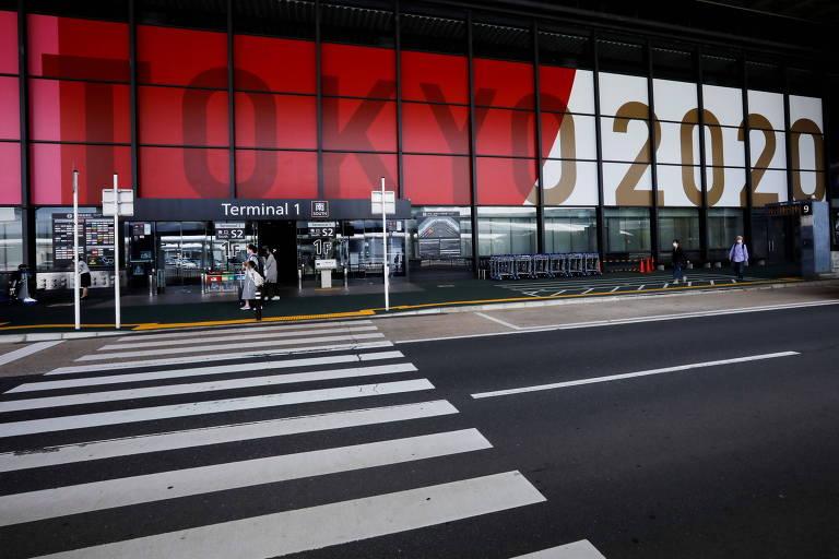 Rua dentro do aeroporto praticamente vazia e iluminada; na parede ao fundo está projetada uma imagem iluminada da bandeira do Japão com as palavras Tokyo 2020