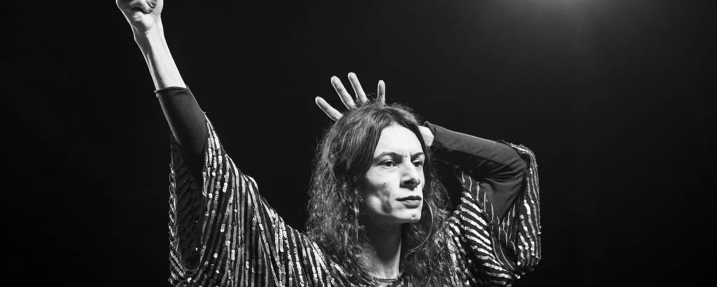 Retrato preto e branco de atriz que simula a estátua da liberdade com uma mão criando a coroa atrás da cabeça e outra simulando segurar uma tocha