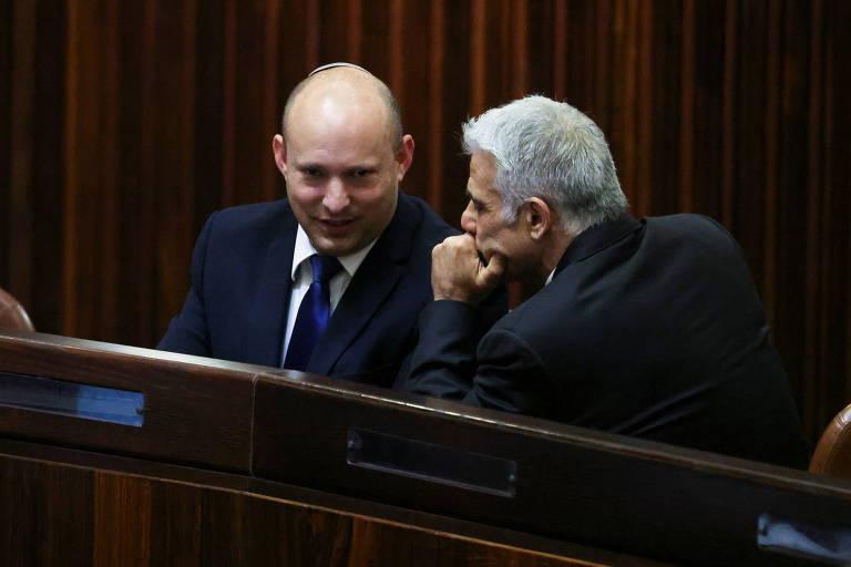 O líder do partido Yamina, Naftali Bennett, conversa com o chefe do Yesh Atid, Yair Lapid, durante sessão especial no Parlamento de Israel, em Jerusalém