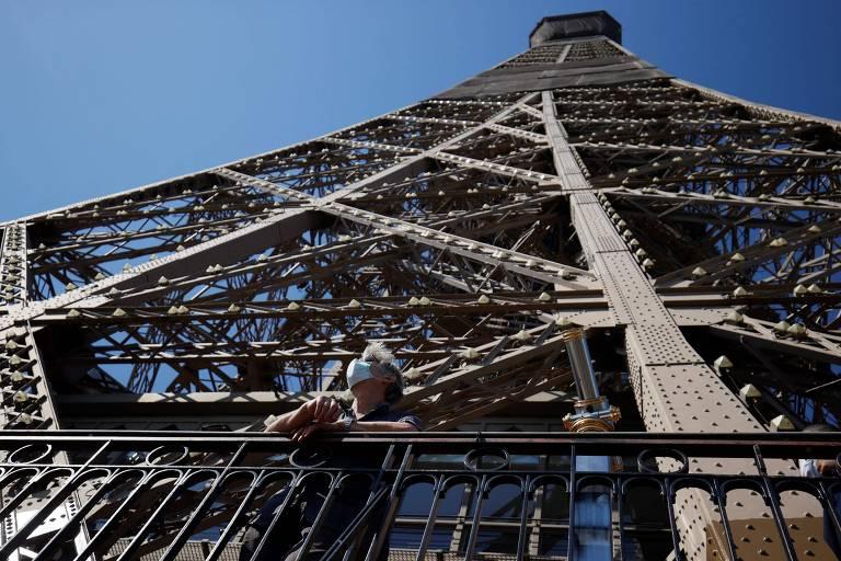De máscara, turista visita a Torre Eiffel, em Paris, França
