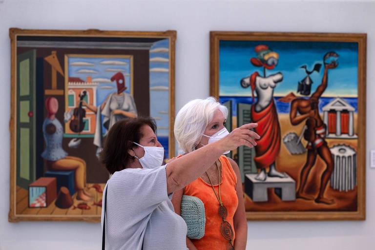 De máscara, mulheres visitam a Galeria Nacional, em Atenas