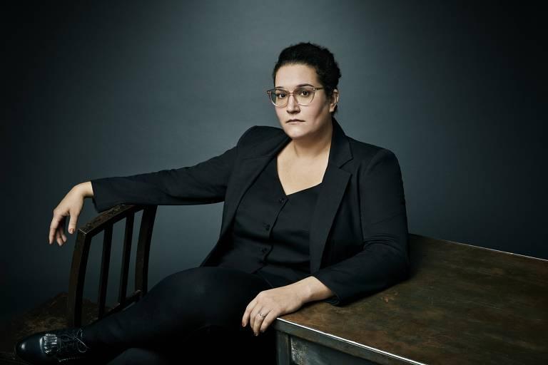 mulher branca de terno e óculos sentada em cadeira