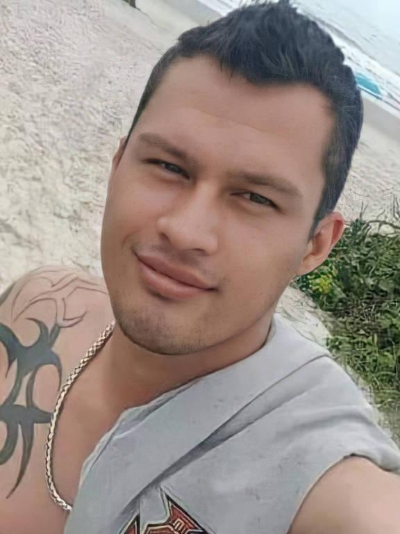 Homem branco tatuado posa em selfie, enquanto está na praia