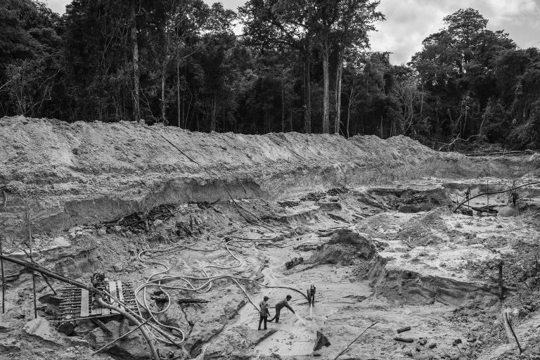 Homens trabalham em área ilegal de mina de ouro no rio Rato, afluente do rio Tapajós, dentro da Floresta Nacional de Itaituba, no Pará