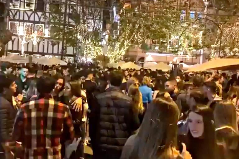 Imagem noturna mostra via lotada, com aglomeração e pessoas conversasndo sem máscaras