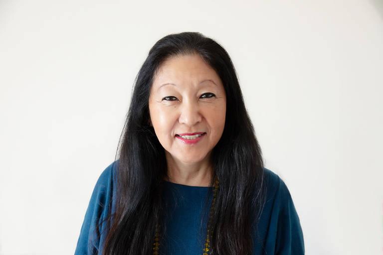Ana Inoue é uma mulher amarela, de cabelos castanho escuro e longos. Ela usa blusa azul marinho e sorri para a foto na frente de um fundo branco