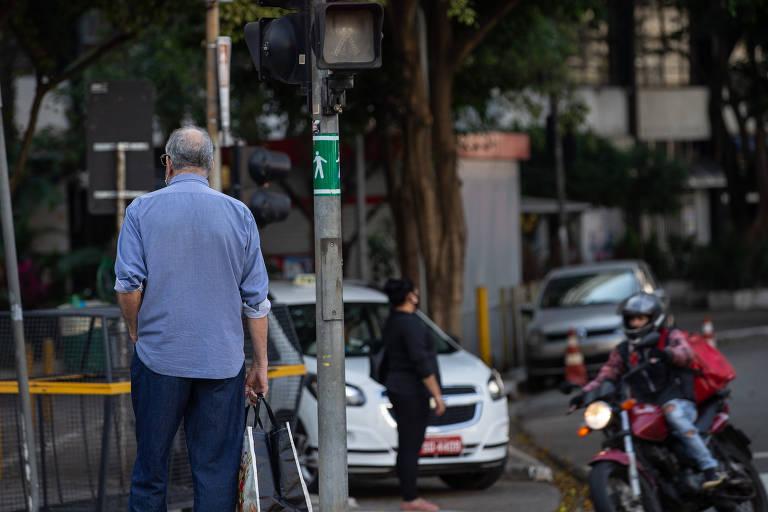 Na foto, idoso aguarda para atravessar a rua na praça 14 Bis, na Bela Vista (região central)