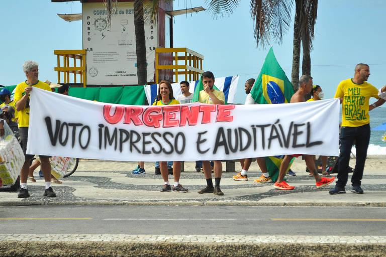 """Homens com camisetas amarelas seguram faixa branca com inscrição """"Urgente"""" em vermelho e, em preto, """"Voto impresso e auditável"""" no calçadão de Copacabana"""