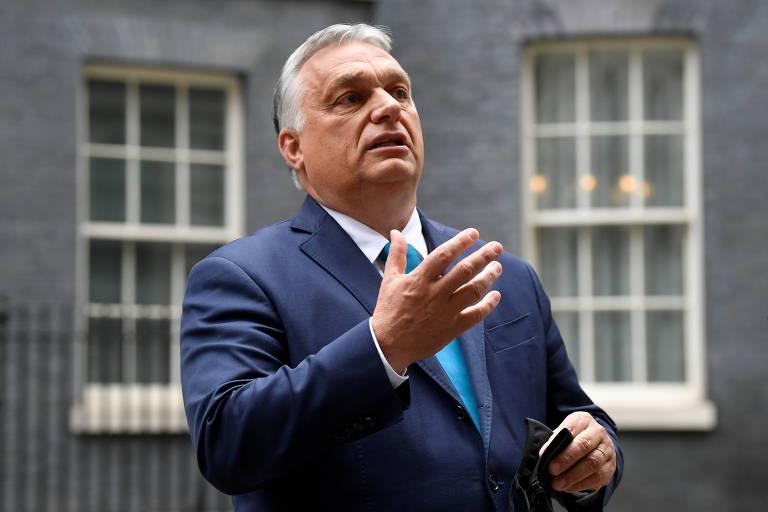 Homem de paletó azul escuro e gravata azul clara, cbelos brancos, gesticula com a mão direita em frente a parede com duas janelas