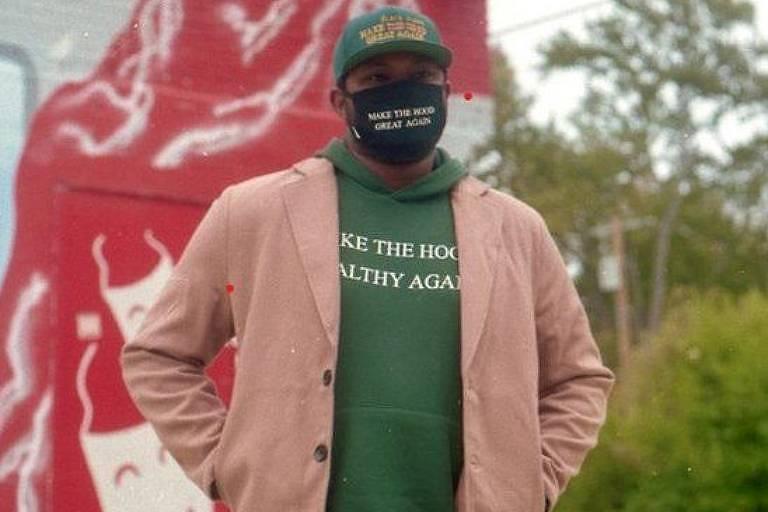 """Um homem negro com casaco bege e moletom verde por baixo do casaco, usando uma máscara de pano com os dizeres """"Faça do gueto bom novamente"""", em referência à frase """"Make America great again"""". Ao fundo, uma parede vermelha com pinturas de máscaras de teatro brancas. Ao lado, a calçada da rua e árvores ao fundo"""