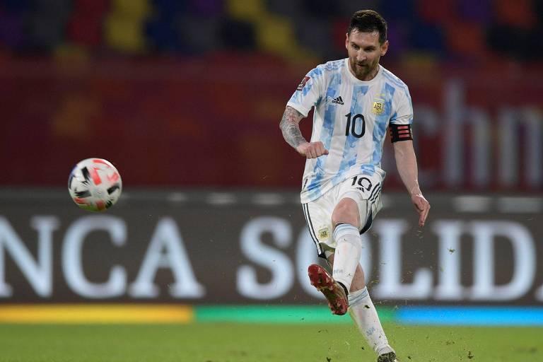 Homem branco com uniforme branco e azul chutando bola