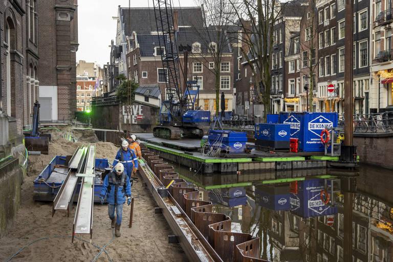 Trabalhadores reconstróem parede de canal no distrito de Grimburgwal, em Amsterdã