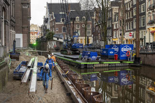Construction workers rebuilding the crumbling canal wall in the Grimburgwal district of Amsterdam on Jan. 8, 2021. (Ilvy Njiokiktjien/The New York Times)