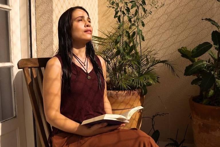 mulher branca de cabelos pretos lisos canta sentada na varanda, cercada de plantas e iluminada pelo sol