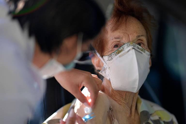 Mulher idosa de máscara branca recebe vacina dentro de carro