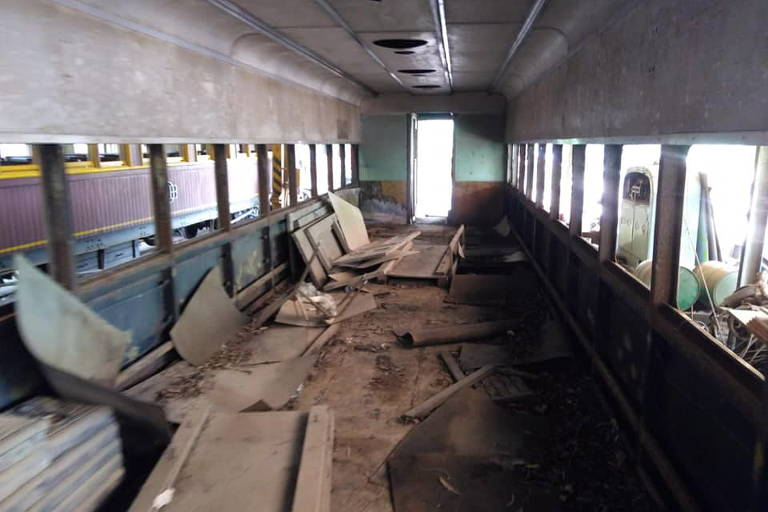 Imagem mostra interior de vagão, sem bancos e danificado