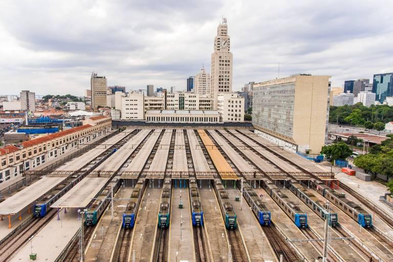 Imagem mostra trens parados num estacionamento, com prédios ao fundo