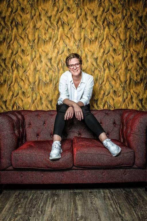 Mulher branca de camisa e tênis brancos sentada no encosto de um sofá avermelhado