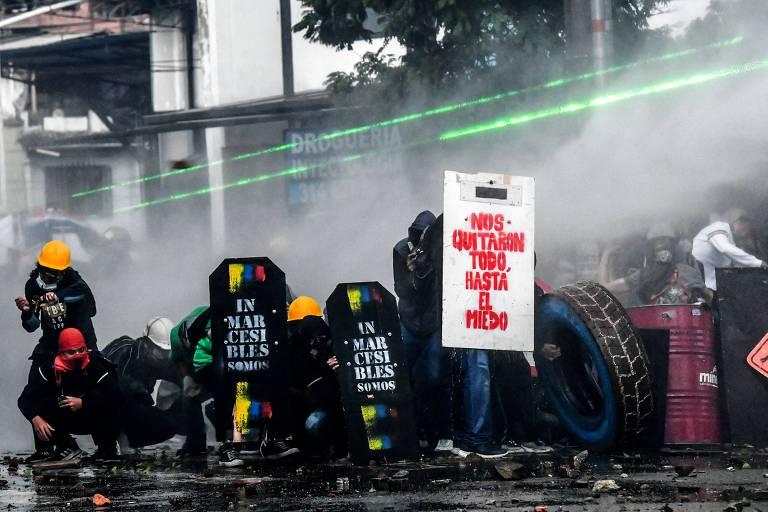 Manifestantes se protegem de jatos de água disparados pela polícia durante protesto em Medellín, na Colômbia