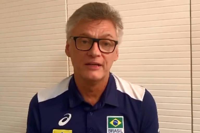 Renan Dal Zotto com uniforme da seleção em frente a uma parede branca