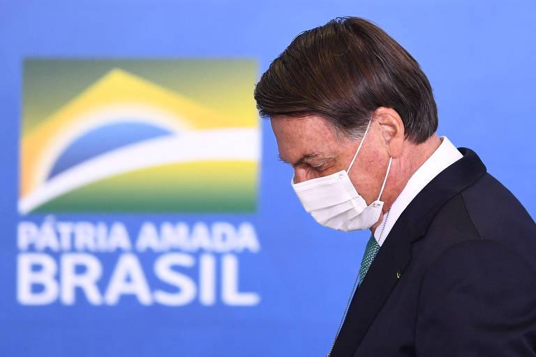"""Bolsonaro de máscara e cabeça inclinada. Ao fundo, os dizeres """"Pátria amada Brasil"""""""