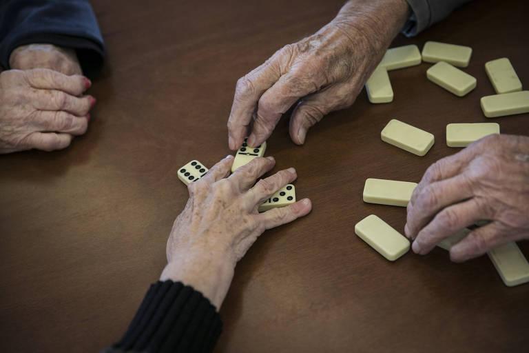 mãos de idosos movimentam peças de dominó