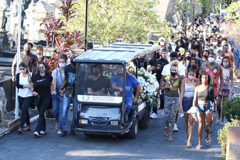 Pessoas seguem carrinho com o corpo da jovem