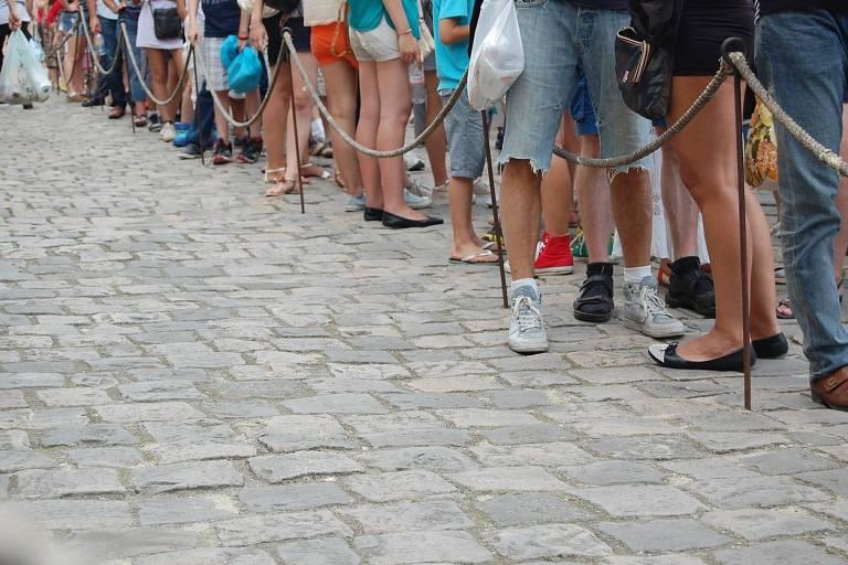 Parte inferior do corpo de pessoas em fila