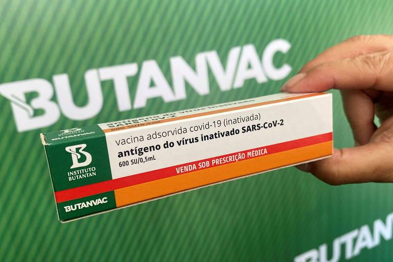 """uma mão segura uma caixa de remédio. no fundo, em letras brancas num fundo verde, """"Butanvac"""""""