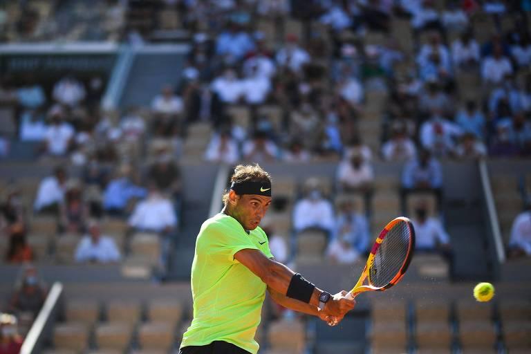 Rafael Nadal bate a bola de backhand; ao fundo, público na quadra Philippe Chatrier