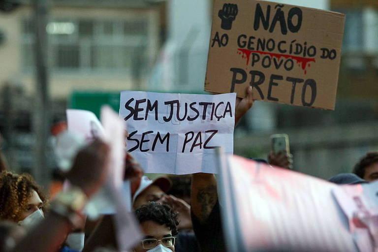 """Pessoas seguram cartazes com dizeres """"Sem justiça sem paz"""" e """"Não ao genocídio do povo preto"""""""