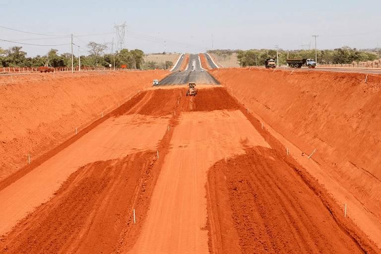 Estrada sendo aberta, de terra, com parte em asfalta mais à frente
