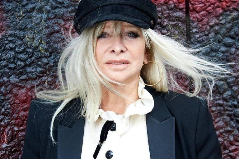 Mulher branca e loira vestindo uma blusa branca com botões pretos e blusa preta