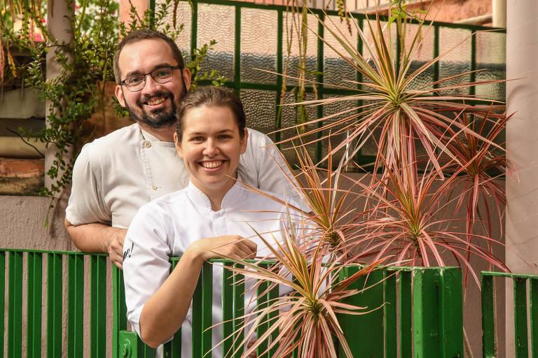 Ygor Lopes e Walyria Fagundes posam atrás de portão verde do restaurante AE!