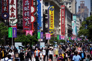 FILE PHOTO: People walk along Nanjing Pedestrian Road during the Labour Day holiday in Shanghai