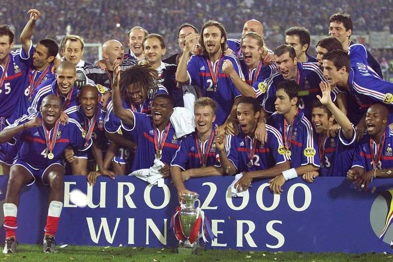 Deschamps, ao centro e segurando a taça, celebra a Euro de 2000 abraçado em Thierry Henry