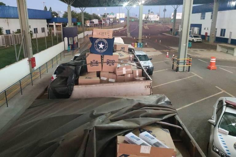 Imagem mostra carroceria de caminhão repleta de caixas de papelão que continham cigarro em seu interior