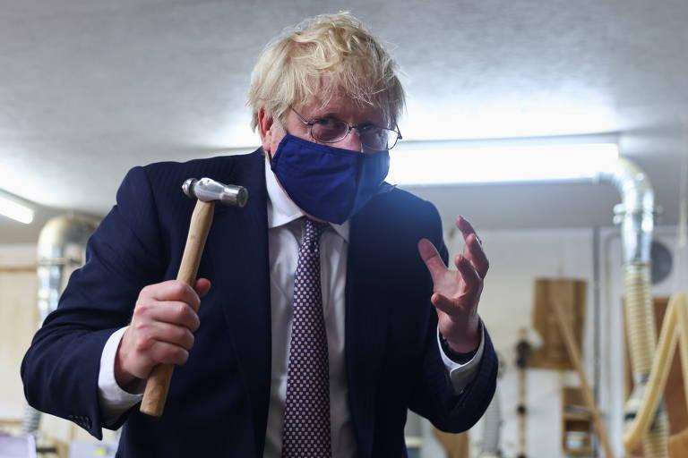 O primeiro-ministro britânico, Boris Johnson, segura um martelo em visita à oficina de Scott Woyka, antes da cúpula do G7, em Falmouth