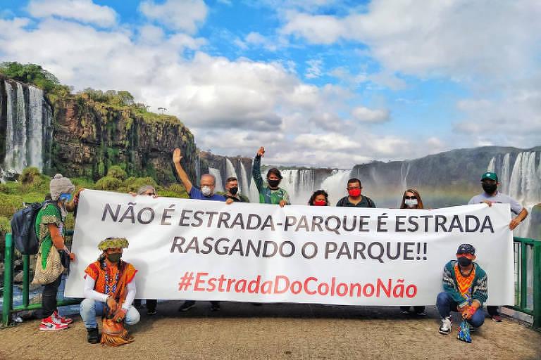 """Ao fundo, as Cataratas do Iguaçu e, à frente, dez pessoas seguram uma faixa com as inscrições """"Não é estrada-parque, é estrada rasgando o parque #EstradadoColonoNão"""""""