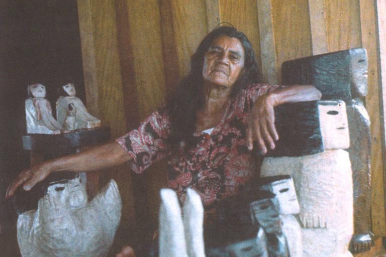 Mulher de cabelos longo em retrato cercada de estátuas de madeira