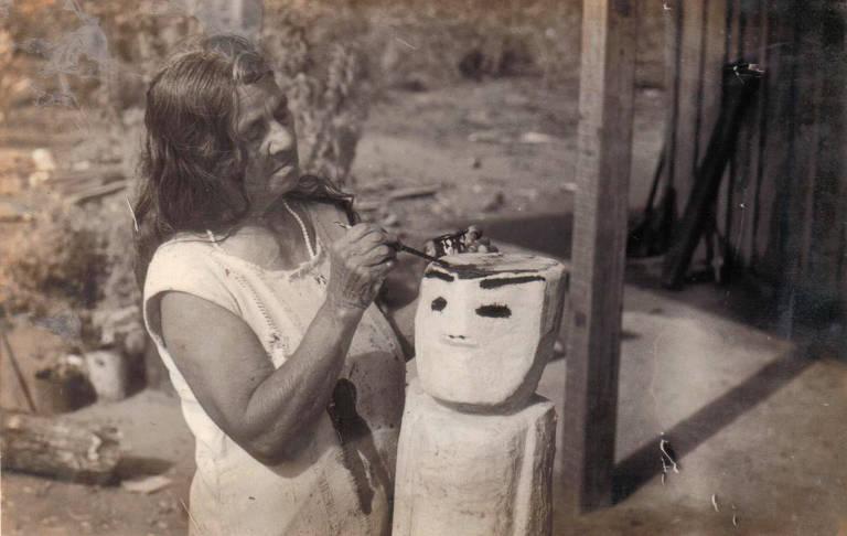 Mulher talha madeira, em retrato preto e branco