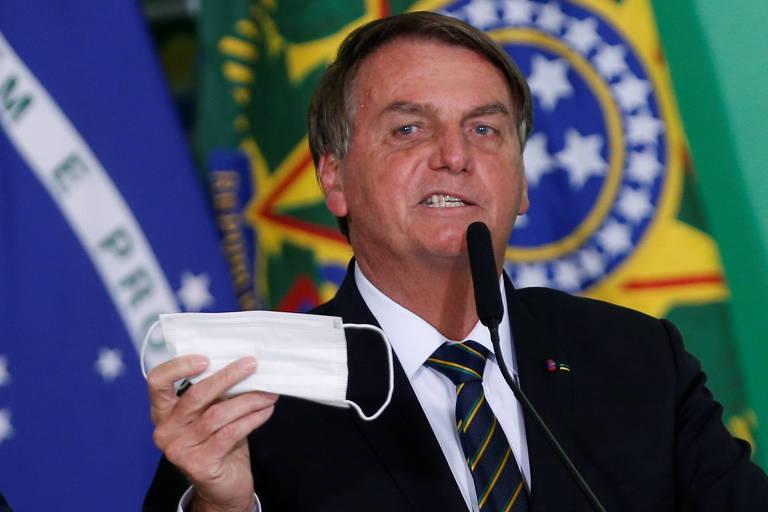 Bolsonaro segura máscara branca longe do rosto, enquanto faz expressão brava, em frente a bandeiras do Brasil