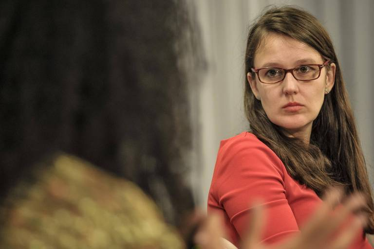 Mulher jovem de óculos e cabelos castanhos compridos, com blusa vermelha, ouvindo outra participante do debate