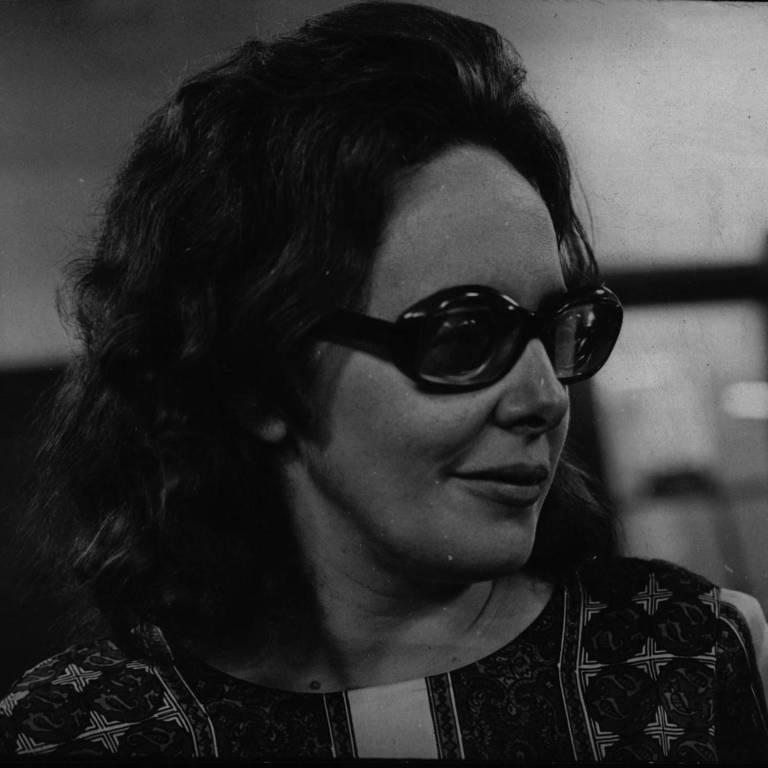 mulher em foto preto e branca de lado com cabelos escuros e óculos de sol