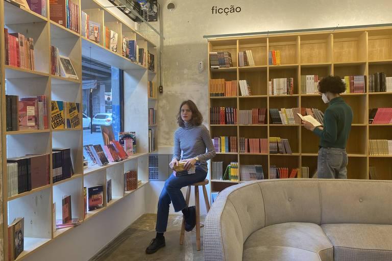 mulher branca de cabelo ate o queixo liso e de cor clara usando jeans e blusa cinza sentada em meio a estantes de livros e um sofá;ao fundo, pessoa de cabelo curto usando mascara mexendo em livro