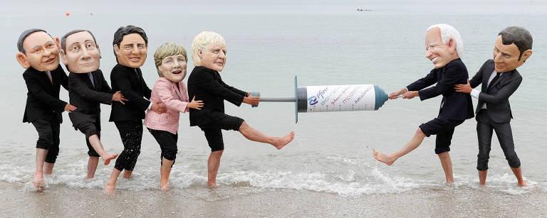 Pessoas com cabeças que simulam as dos líderes do G7 puxam uma seringa gigante como se fosse um cabo de guerra