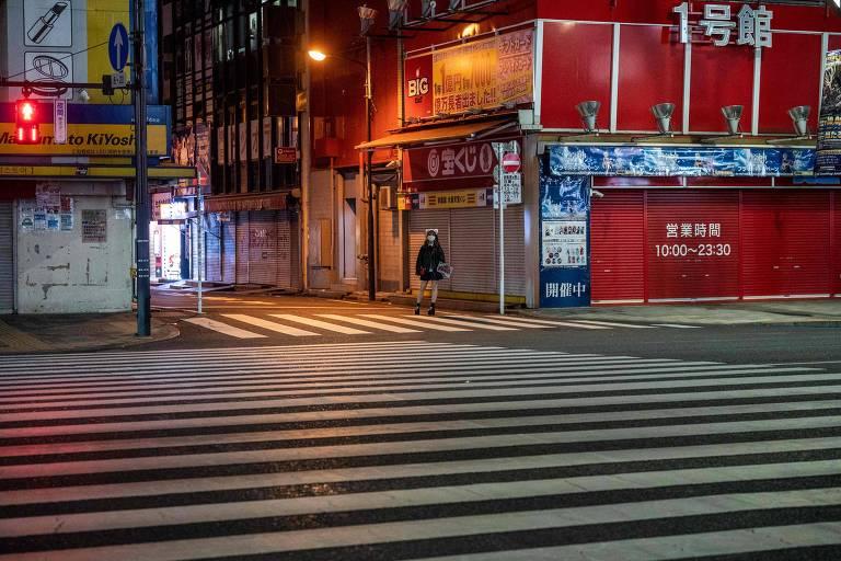 Funcionária de bar exibe preços do estabelecimento em rua do distrito Akihabara, em Tóquio