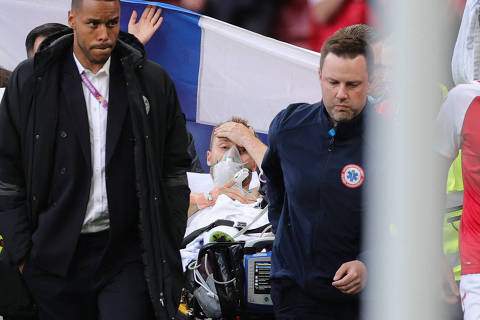 TOPSHOT - Denmark's midfielder Christian Eriksen (C) is evacuated after collapsing on the pitch during the UEFA EURO 2020 Group B football match between Denmark and Finland at the Parken Stadium in Copenhagen on June 12, 2021. (Photo by Friedemann Vogel / various sources / AFP)