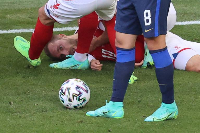 O meio-campista Eriksen, da Dinamarca, cai no gramado, sozinho, e preocupa imediatamente colegas e adversários